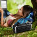 Bluetooth Lautsprecher neben einer Frau die im ebook reader kießt